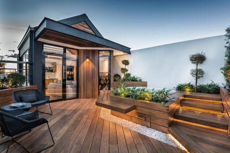 This modern rooftop terrace features hidden lighting that creates a calming ambience, built-in bench seating, and a spa that's surrounded by plants. The plants that are used on the deck also provide an element of privacy to the area.