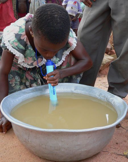 LifeStraw® is a portable water filter that effectively removes all bacteria and parasites responsible for causing common diarrhoeal diseases. LifeStraw® requires no electrical power or spare parts and can be carried around for easy access to safe and clean water. - Image of child drinking water from bowl through LifeStraw <3