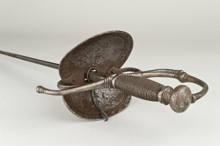 """Museo Arqueológico Nacional Espada ropera de acero tipo """"de concha"""", con guarnición simple de lazo. Los gavilanes de la cruz están curvados en sentidos opuestos. Posee hoja de dos mesas, acanalada en su primer tercio. A partir del siglo XVI, la pesada espada medieval empezó a sustituirse por el estoque y la espada ropera, donde primaba la fortaleza del brazo y la destreza. En el siglo XVI el mango evoluciona dirigiéndose hacia el pomo y formando los guardamanos, multiplicándose las guardas…"""