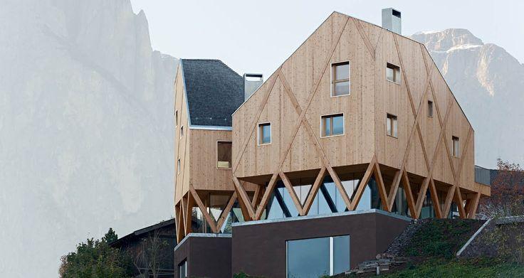 Ce bâtiment qui s'érige sur une colline à Castelrotto, en Italie, attire de suite le regard. Autant par sa forme globale tout en hauteur que par sa conception en V des niveaux inférieurs. Autre originalité, l'utilisation des matériaux par strates, ossature et niveaux supérieurs en bois, un étage exclusivement en parois de verre et rez-de-chaussée et cheminée en béton. Pour l'aménagement, on retrouve l'atelier de l'artiste en bas et l'habitation dans les étages.