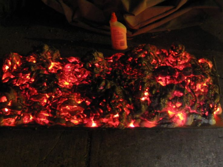 DIY glowing coals project with cardboard, foam, string lights, plastic bottles and paint