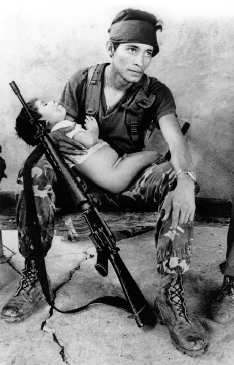 May 1984 — A young child sleeps in the arms of a Salvadoran Soldier with an automatic weapon leaning against his knee, after field operations in the Cabañas province in El Salvador. The Soldier is one of about 3,000 government troops that participated in an anti-guerrilla operation.