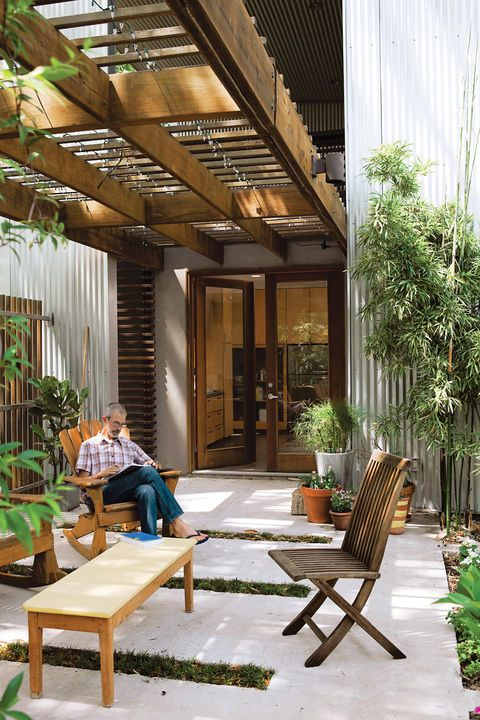 Catovic Hughes's design for the Morelands is all about embracing the outdoors. Rick spends as much time on the patio as he can. The undulation of the aluminum cladding makes a regular, rhythmic backdrop for the yards-high bamboo he lovingly tends.  Courtesy of Joao Canziani.