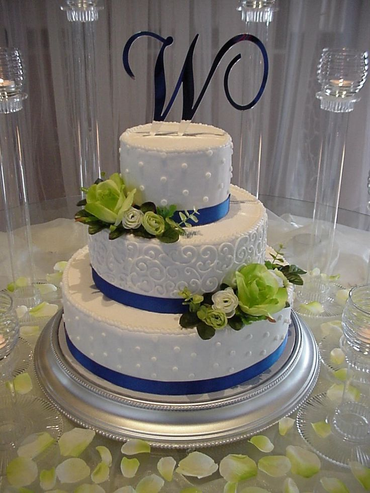 Apple green roses with blue ribbon dots and swirls - 14,10,6 inch round cakes with buttercream frosting white dots and swirls, green silk roses and royal blue silk grosgrain ribbon.  Candles and rose petals finish the look.