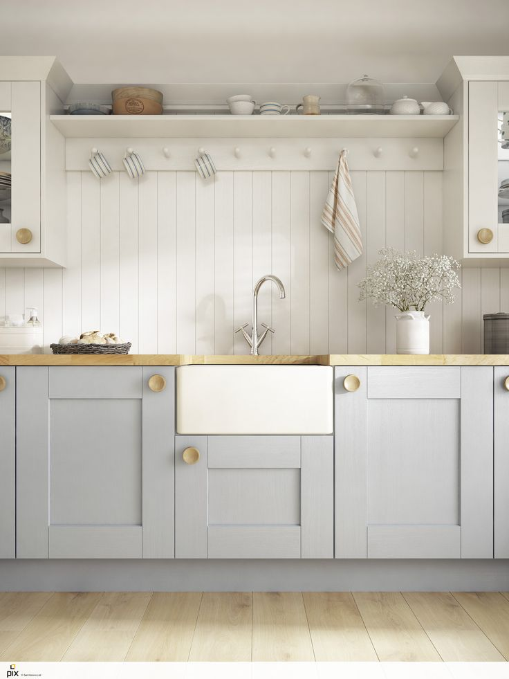 Soft white panelled walls with wooden pegs to hang a collection of coastal style mugs. The butler sink with the solid oak worktop are key to the New England style. Painted blue shaker doors adds colour and great interior inspiration. CGI photography by http://setvisionspix.co.uk/