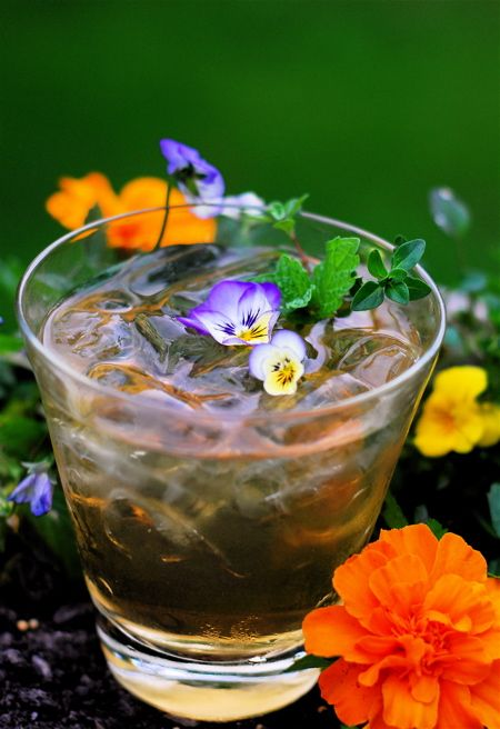 Secret Garden Iced Tea Cocktail  ice, add a shot of vodka or Jeremiah Weed bourbon Whiskey, add a shot of herbal simple syrup, top off with cold iced tea and a splash of club soda,  garnish with violas, herb sprigs and a lemon wedge
