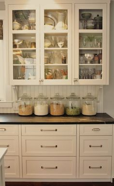 Amazing kitchen design with white shaker glass-front kitchen cabinets painted Benjamin Moore White Dove, beadboard backsplash, soapstone counter tops and glass canisters.