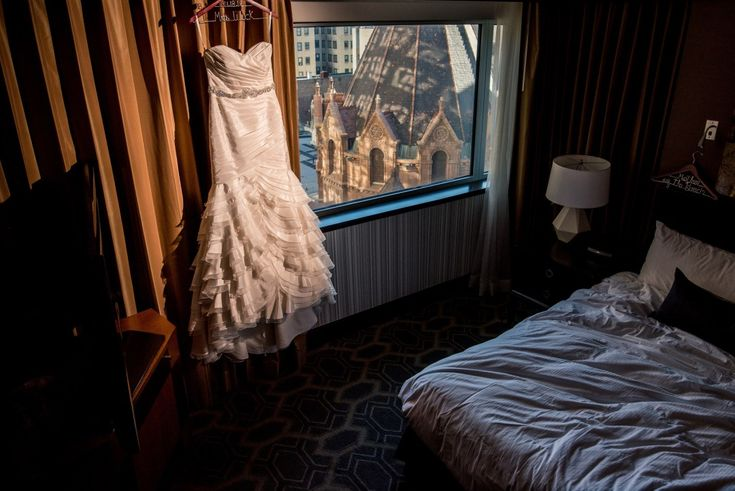 Wedding dress hangs near window in Sofitel Hotel room