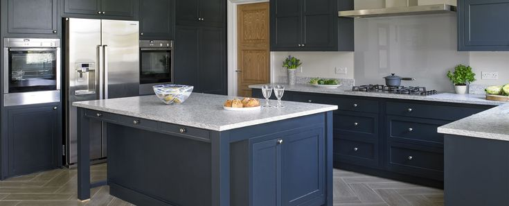 Esher Kitchen This bold, bespoke family kitchen design was custom created for this light and spacious family home in Esher, Surrey. Tall dark cabinets house a generous pantry and breakfast cupboards. Light granite counter tops provide a contrast to the deep blue finish of the cupboards. The large American fridge freezer #LuxuryFridges