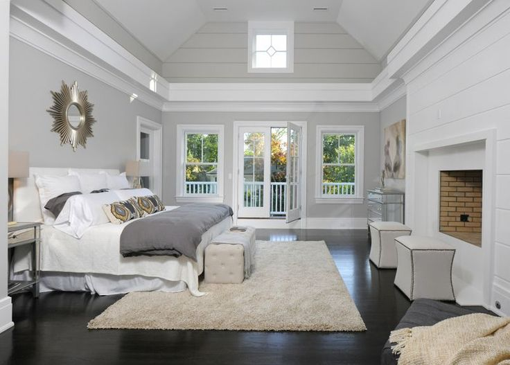 A master bedroom with a fireplace, skylit cathedral ceiling and a Juliet balcony.