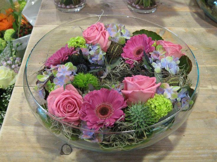 Een mooi bloem arrangement, een krans gemaakt in een glazen schaal. Bloem soorten: Gerbera's, Rozen, Dianthus, Viburnum en exotische vruchten.