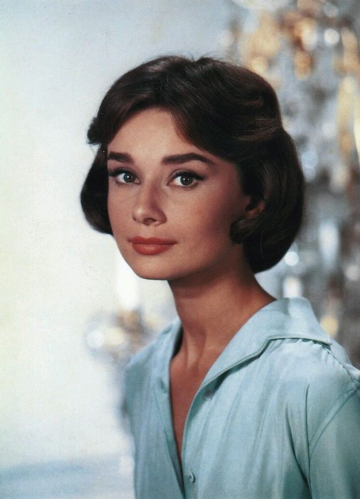 """The actress Audrey Hepburn photographed by Willy Rizzo at the Studios de Boulogne, on Avenue Jean-Baptiste-Clément, in Boulogne-Billancourt, a commune in the western suburbs of Paris (France), during break in the filming of """"Love in the Afternoon"""", in September 1956.Note: Her hairstyle called """"Paris heart"""" was created by the famous American hairdresser Kenneth Battelle."""