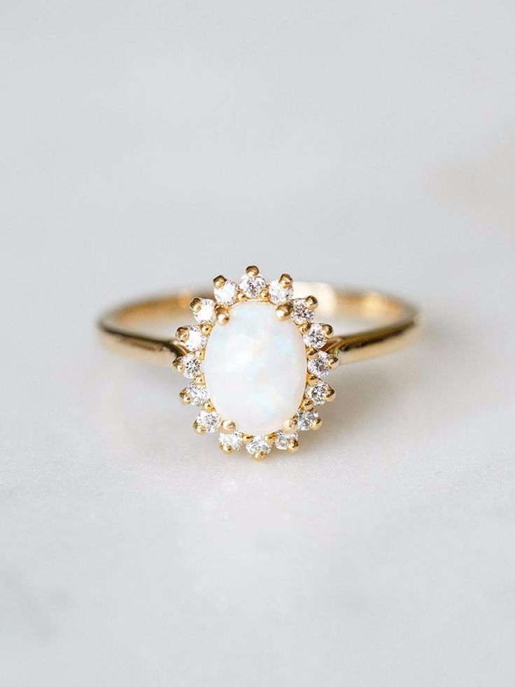 Spectacular fire opal surrounded by a halo of tiny diamonds. See more here: https://www.davieandchiyo.com/collections/lifestyle-rings/products/aurora-ring