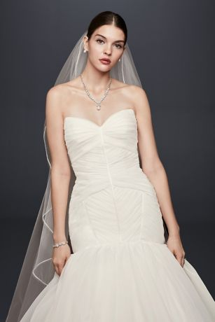 Zac Posen\'s signature couture craftsmanship is highlighted in this draped organza trumpet wedding dress. The drop-waist bodice is defined by angular pleats and satin seaming and leads to a soft trump
