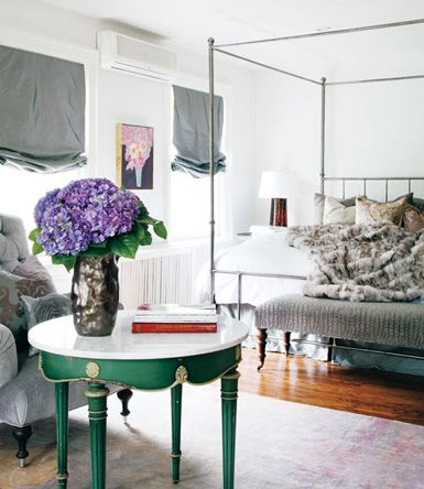 green table with marble top + bronzy vase + purple hydrangeas + sunny bedroom