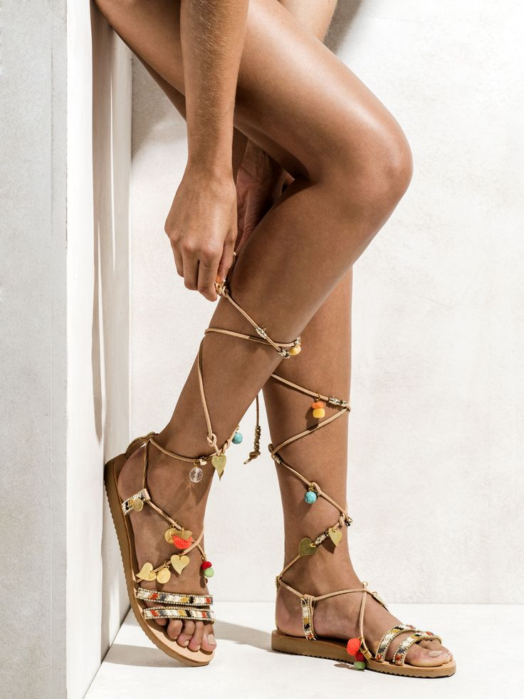 Handmade tie up gladiator sandals embellished with various semiprecious stones, pom poms in neon orange, cute shiny metal hearts, and small metal charms. http://www.elinalinardaki.com/shoes/sandals/all-time-classics/sandal-stardust/