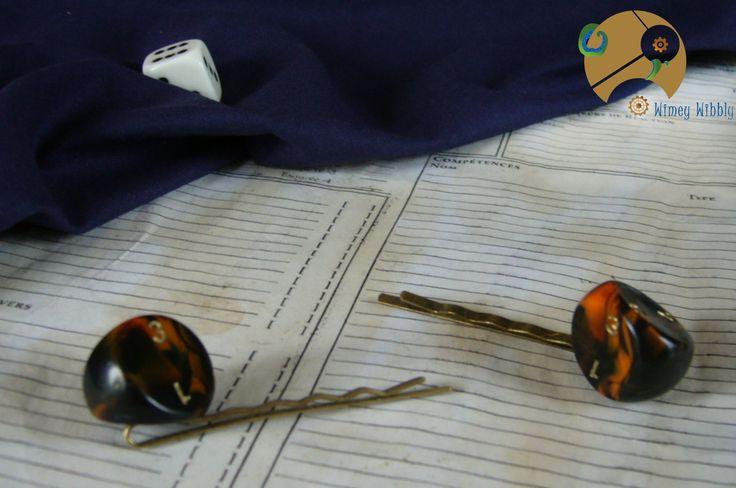Epingles à cheveux Oreilles de Geek, très originales : placées de chaque côté de votre tête, elles ressembleront à des oreilles de chat ou de petites cornes grâce à la forme de leurs dés pyramidaux arrondis à cinq faces, utilisés en jeu de rôle (appelés d3).  Avec leur belle teinte bicolore marbrée noir et orange, elles enflammeront vos coiffures !  9,50 euros la paire