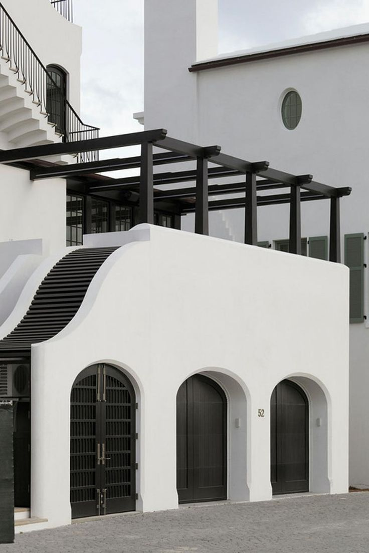 Crisp white stucco pairs with black doors, a black pergola and black accents to create a high-contrast look for this home's exterior. The striking color palette adds an element of drama to the Mediterranean design.