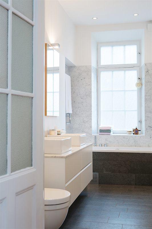 badrum klätt i delvis marmor och kalktensgolv