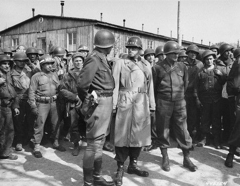 Patton with his famous sidearm in view and General Bradley on a tour of the newly liberated concentration camp at Ohrdruf.