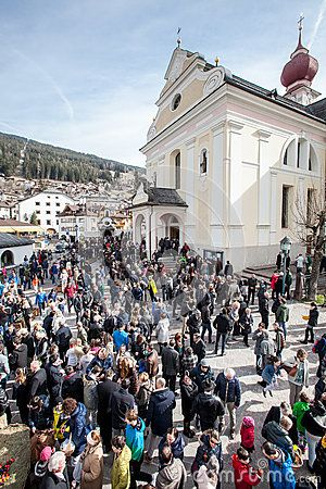 Church and crowd of faithful. Easter in Ortisei, Italy.