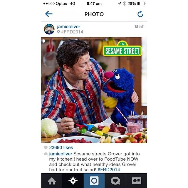 Jamie wearing the Three Over One Tommy Shirt, with Grover on Sesame Street.