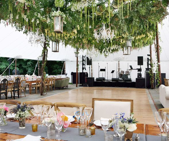 Chandeliers, lanterns and lush fresh blooms are suspended overhead.