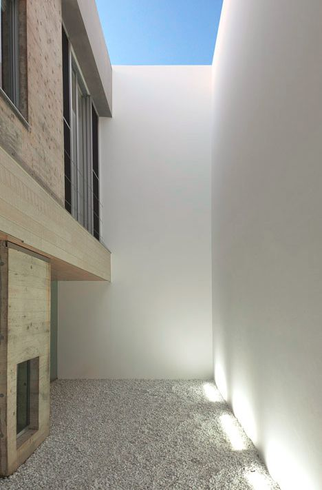 blank house interior courtyard-blank box-Designed by Tsukano Architect Office, the exterior is a single (nearly uninterrupted) wrapping white plane, as plain as you could possibly imagine, set on a light-gray slab.