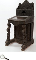 A rosewood carved davenport, in Anglo-Indian manner, with profusely carved design of Lord Krishna playing the flute in the centre of thick foliate surrounding on the cornice and with beasts and other traditional designs in the lower section, the raised superstructure fitted with a bank of drawers over a hinged writing slope and fitted four side drawers enclosed by a cupboard door.     26 in L x 27 in B x 54 in H