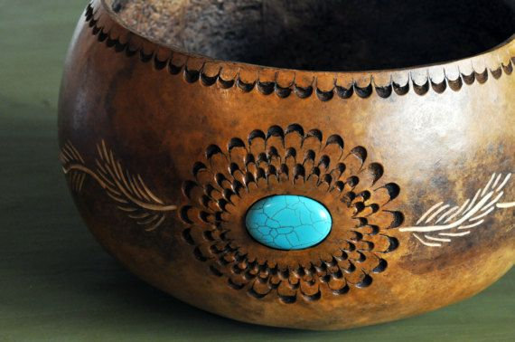 A handcrafted gourd bowl with a design of chip carving that surrounds a turquoise stone, this carved gourd bowl, made from a real gourd, is a work of art! If you like natural decor and brown tones with a splash of color, this item is for you! Starting with the natural amber of the
