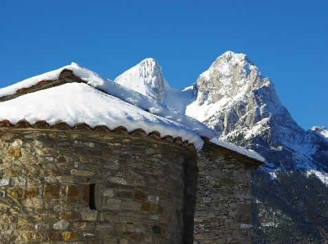 Catalan snow-covered singular mountain, with Romanesque hermitage.