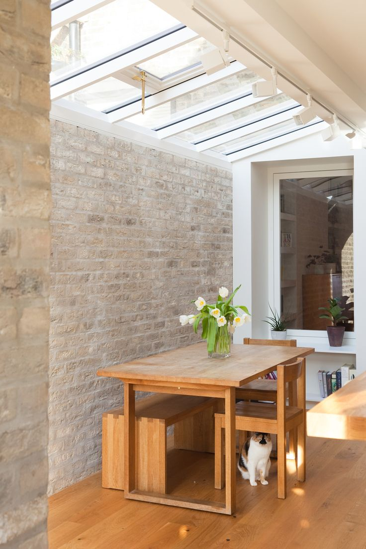 Roof lights flood the dining area with light. Exposed brick walls. Internal window seat allows connection between double reception and new side extension.