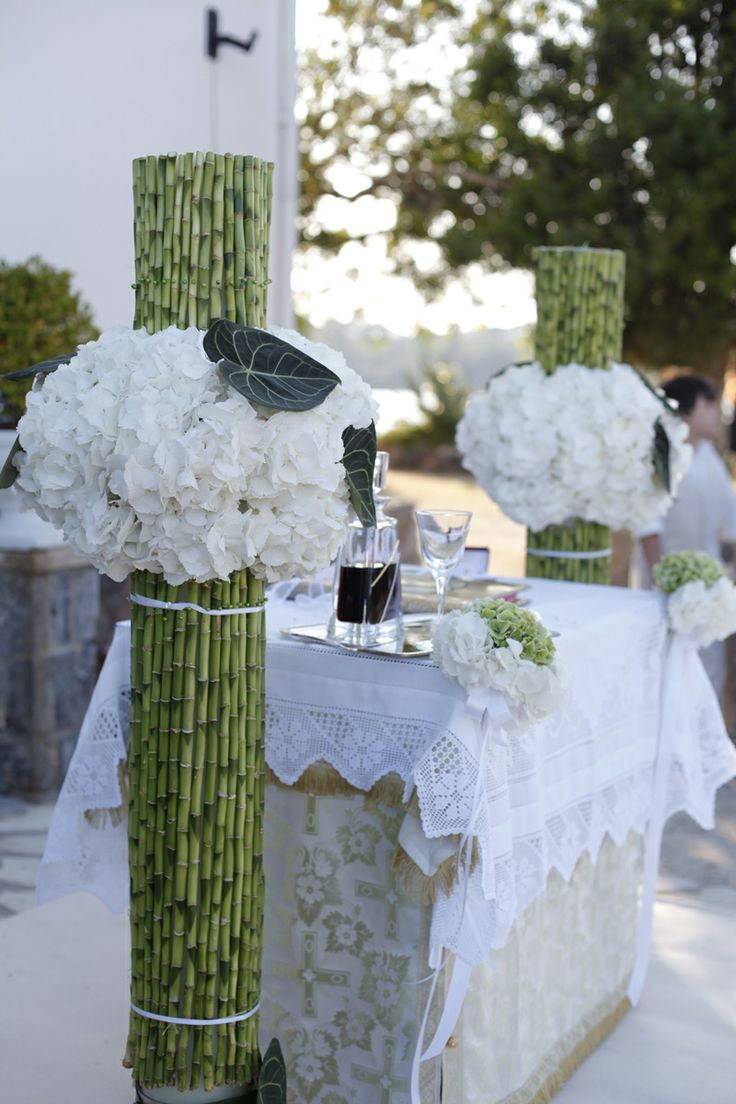 Orthodox wedding ceremony  Keyhole View: Ethnic Wedding Candles made of bamboo and all white peonias.