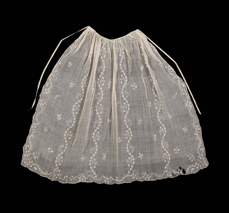 White muslin embroidered with white linen threads. Flowering vines and sprigs of flowers. Long and short, stem, chain stitch, drawn work. Apron gathered to a silk gros grain ribbon tie at waist. A few brown spots and holes in left corner ofapron.