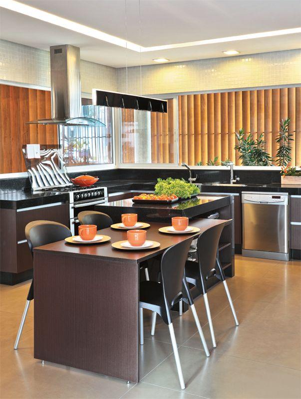 Na cozinha planejada, as bancadas empregam granito preto são gabriel. Acoplada à ilha central, está a mesa de refeições rápidas. As janelas que cercam o ambiente e dão para a fachada, em frente, e para a garagem, na lateral, foram protegidas pelos brises de cedro maciço.
