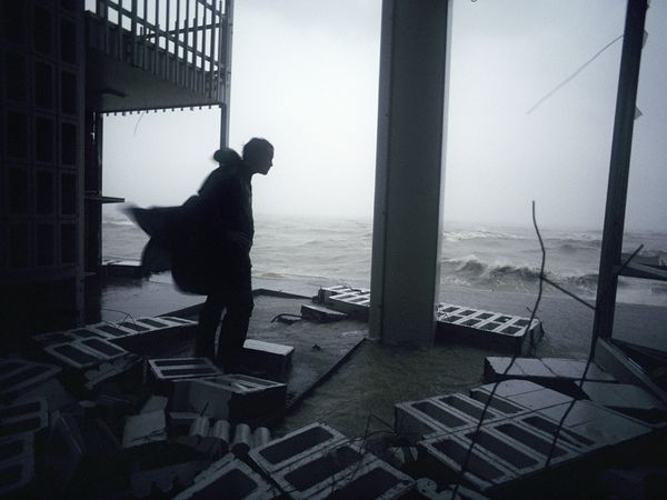 Photo: Man observes hurricane damage as winds reach 100 mph