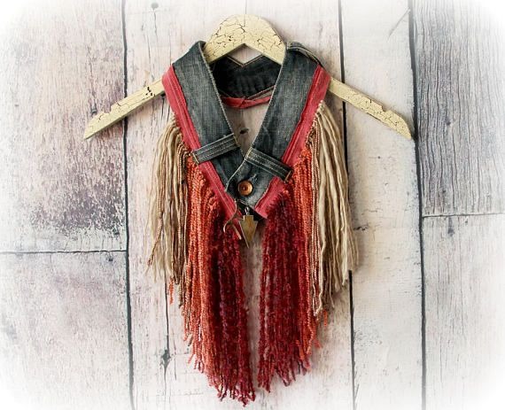 DESIREE Fringed Scarf/Necklace  This one of a kind scarf/necklace features a jeans waistband that goes around the neck and buttons closed at the front. Fringe in earthy, ombre colors was added in a mix of textured yarn. Arrowhead and antler charms adorn the center of this unique