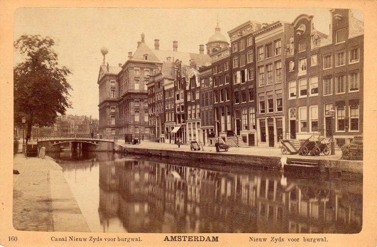 Op deze mooie en zeer zeldzame foto is de Nieuwe Zijdsvoorburgwal  mooi te zien. De  opname is van voor 1884 toen werd de burgwal gedempt. De Pijpenmarkt zo werd de overzijde van de wal genoemd.