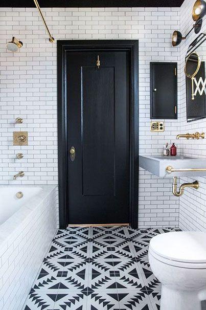 Une salle de bain en carrelage noir et blanc avec robinetterie dorée