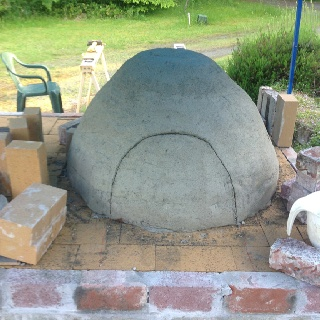 Wood fired clay oven (under construction). First layer of dense material on and drying. Door opening cut. Next steps: 1. take out the cut door and take out the sand form. This will help it to dry further. 2. Build the brick door arch. 3. Lay down insulating layers. 4. Dry. 5. PIZZA!   If the weather cooperates.... Should be baking in 2 weeks.