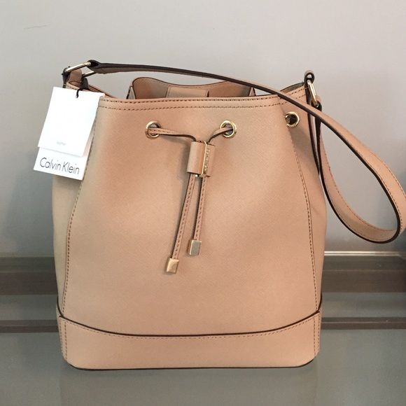 Calvin Klein Saffiano Leather Bucket Bag Such a gorgeous handbag. It's brand new with the tags and has never been used. Perfect condition - no signs of wear or imperfections of any sort! Rich nude color with gold hardware. Perfect size bag for everyday use! As you can read from the tag, this bag is real leather and is definitely made to last. Super good quality & a timeless bag that will never go out of style! Calvin Klein Bags