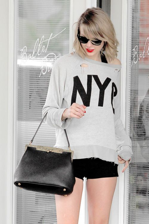 Tay Tay looking fabulous in a grungy sweatshirt, fab shorts, and a perfect purse.