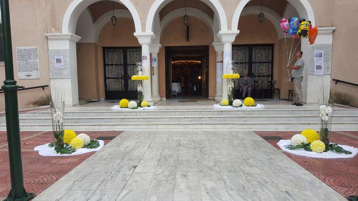 Γάμου στολισμός εξωτερικά στην εκκλησία με μπάλες από λουλούδια και γυάλινα βάζα με ορχιδέες φαλαίνοψις.