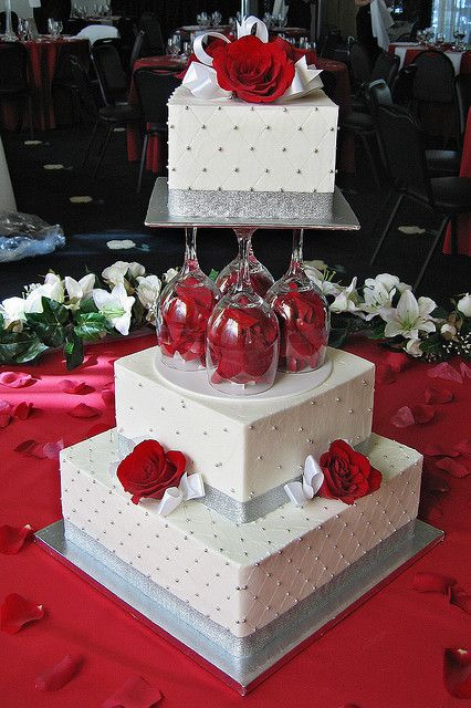 Pretty red and white wedding cake with roses and wine glasses! How creative