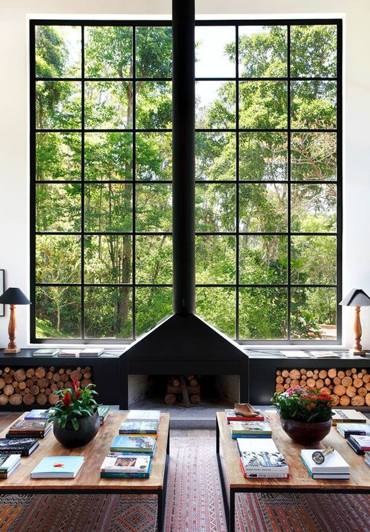 Love this - large windows with the fireplace and wood storage