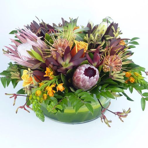 Full Bloom Flowers - Tropical floral centre piece for the series mistresses using various protea leucodendron orange ornithagalum kangaroopaw, succulents.