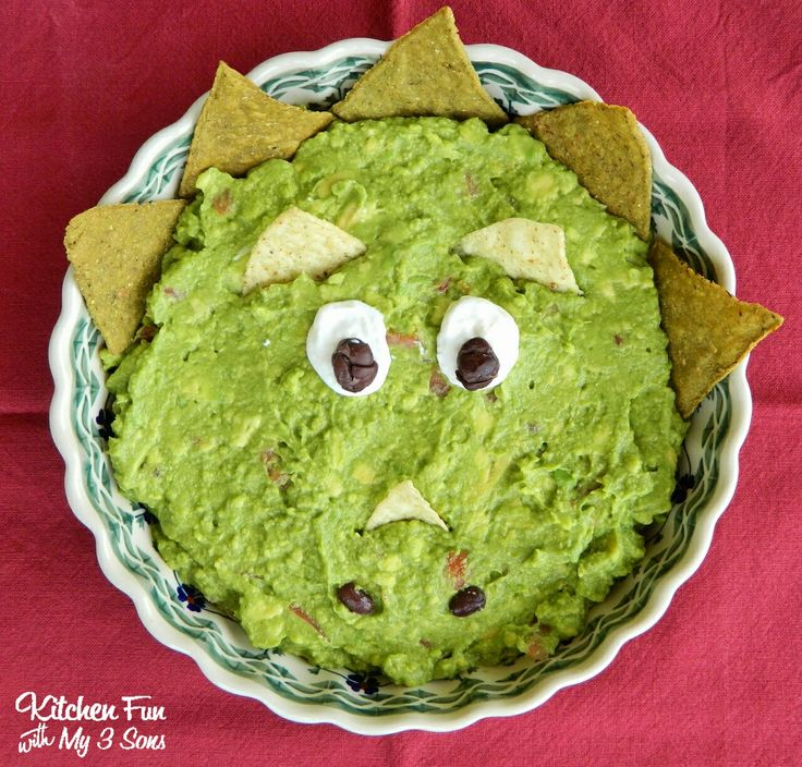 Dinosaur Guacamole dish decorating with chips, sour cream, & black beans