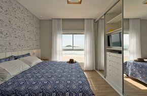 Decoração de apartamento de praia. Quarto de casal com tons neutros, parede de tijolinho branco, guarda roupas espelhado e roupa de cama azul. #casadevalentina #decoracao #decor #design