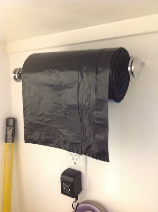 28 Brilliant Garage Organization Ideas | Use a paper towel holder for garbage bags.