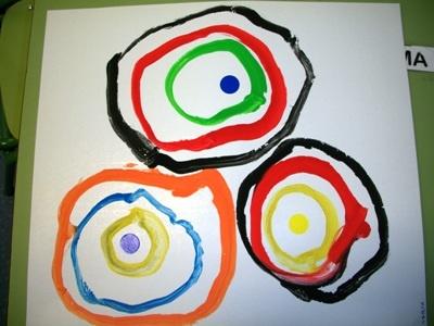 pegar 3 gomets(cercles) en un full.En pintura de diferents colors tenien que envoltar els cercles de manera que s´apareguera a una diana.